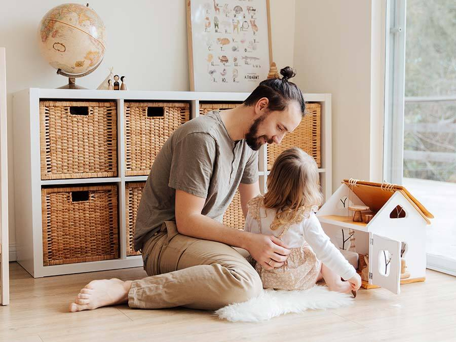 Ein Vater spielt mit seiner kleinen Tochter. Er ist zuhause und erhält Kinderkrankengeld.