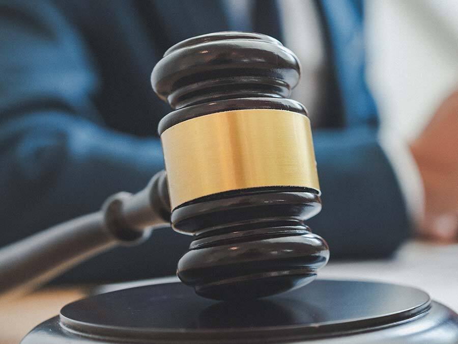 Ein Richterhammer symbolisiert, dass der Streit um den Entzug des Pflichtteil oft vor Gericht endet.
