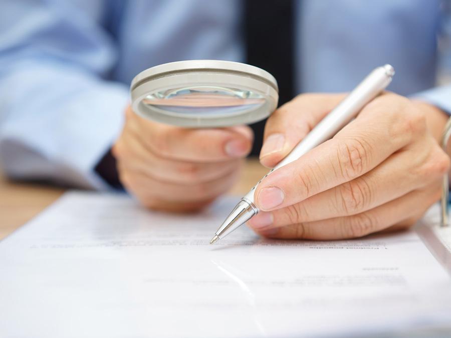 Ein Mieter prüft mit der Lupe die Zahlungsbelege für seine Betriebskostenabrechnung.