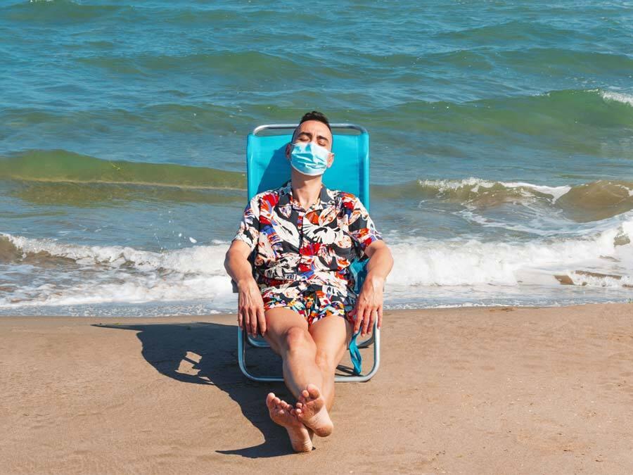 Arbeitnehmer verbringt Strandurlaub mit Maske, weil der Chef Betriebsurlaub wegen Corona anordnet.