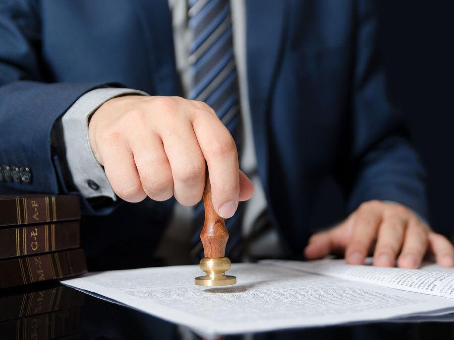 Ein Notar setzt sein Siegel unter einen Erbvertrag.