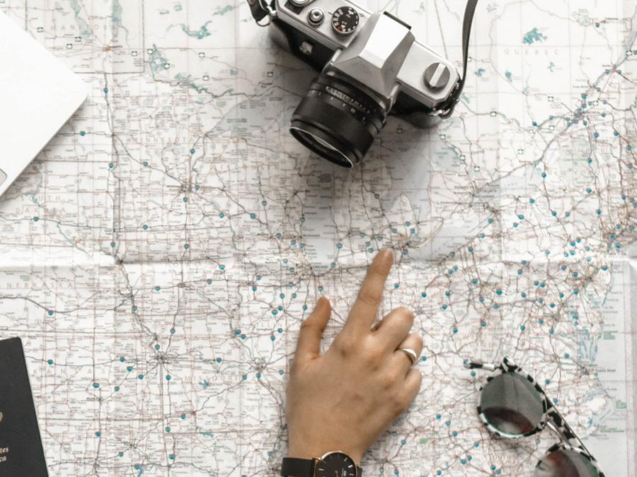 Ein Arbeitnehmer sucht sich auf der Landkarte das Ziel für den nächsten Urlaub aus. Er möchte den Urlaub ins nächste Jahr mitnehmen.